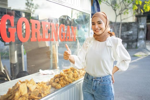 Een mooi meisje in een sluier met duimen omhoog die verschillende soorten gefrituurd voedsel verkoopt met behulp van een kar