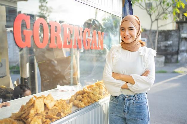 Een mooi meisje in een sluier met gekruiste handen die verschillende soorten gefrituurd voedsel verkoopt met behulp van een kar