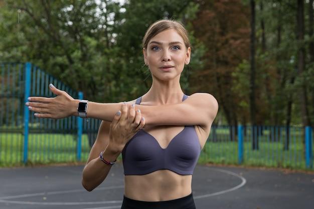 Een mooi meisje in een sporttop en legging traint op een basketbalveld in het park