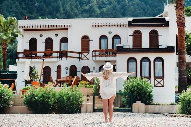 Een mooi meisje in een tuniek en hoed staat in de buurt van een villa met een prachtig uitzicht. een vrouw geniet van een vakantie in een turks resort.
