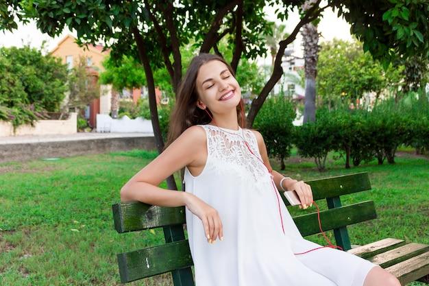Een mooi meisje in een witte jurk luistert naar haar favoriete liedje op de bank in het park. ze geniet en heeft plezier.