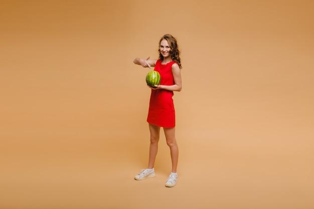 Een mooi meisje in glazen en een rode jurk heeft een watermeloen in haar handen.