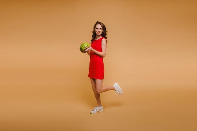 Een mooi meisje in glazen en een rode jurk heeft een watermeloen in haar handen