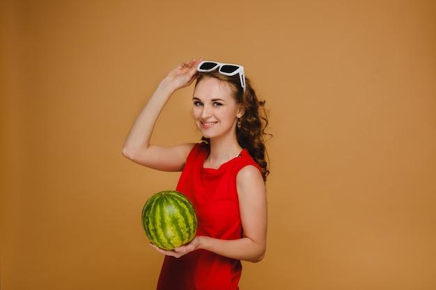 Een mooi meisje in glazen en een rode jurk met een watermeloen op een sinaasappel.