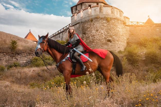 Een mooi meisje in het kostuum van de krijgerskoningin. een vrouw te paard met een zwaard in haar hand.