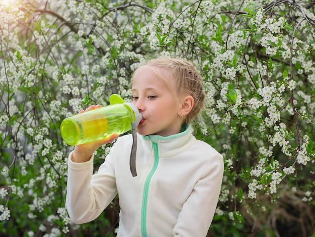 Een mooi meisje in het voorjaar park lest haar dorst met water met citroen en munt.