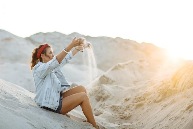 Een mooi meisje in jeans, korte broek, een rode hoepel en een witte bh zit op het zand