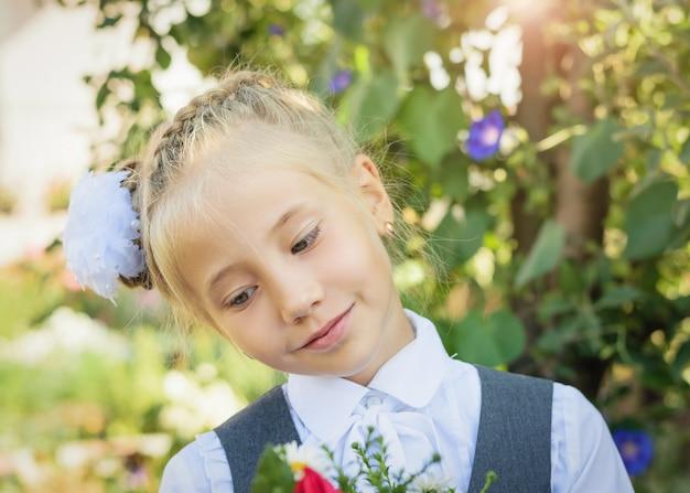 Een mooi meisje in schoolkleding en een boog op haar hoofd staat in de buurt van een boom.