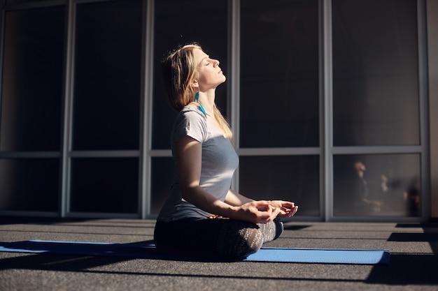 Een mooi meisje in sportkleding mediteert tijdens yogalessen. de blonde zit in de lotuspositie, ontspant en stelt haar gezicht bloot aan de zon. het concept van een gezonde levensstijl. zijaanzicht