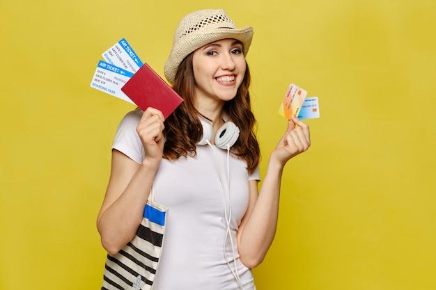 Een mooi meisje in vrijetijdskleding houdt een paspoort en vliegtickets met creditcards.