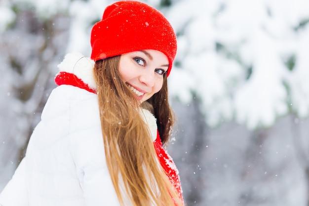 Een mooi meisje in winterkleren kijkt glimlachen