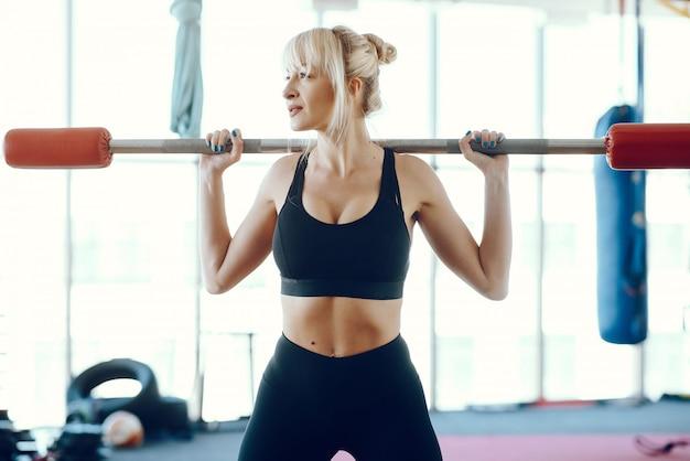 Een mooi meisje is bezig met een sportschool