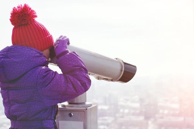 Een mooi meisje kijkt door een verrekijker vanaf het dak naar beneden en maakt foto's met de camera.