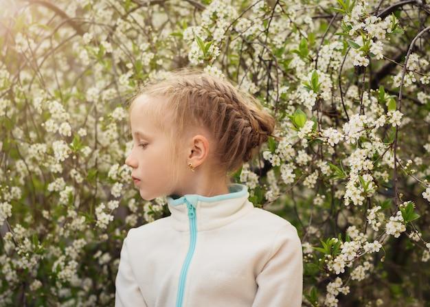 Een mooi meisje kijkt naar de rechterkant in de kersenboomgaard.