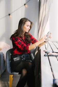 Een mooi meisje kijkt naar zichzelf in de tafelspiegel bij het raam. ik ga haar make-up doen