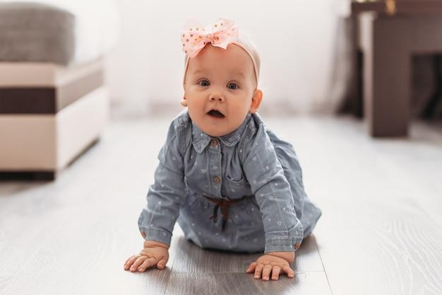Een mooi meisje kruipt op de vloer in de kamer. een kind leert kruipen