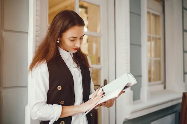 Een mooi meisje leest een tijdschrift in een café