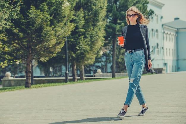 Een mooi meisje loopt onderweg over straat met een kop koffie.