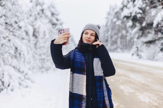 Een mooi meisje maakt een selfie in het midden van een besneeuwde bosweg