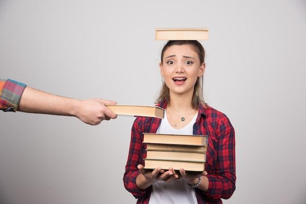 Een mooi meisje met een boek op haar hoofd Gratis Foto