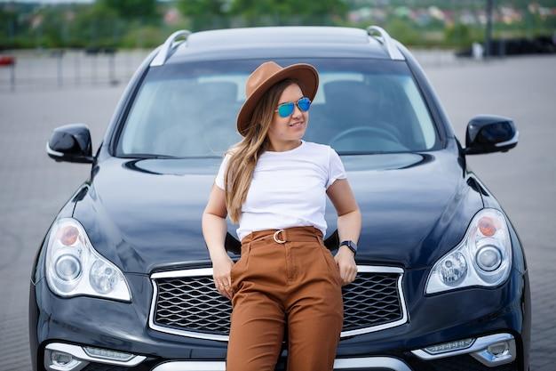 Een mooi meisje met een bril en een bruine hoed staat in de buurt van een zwarte auto. jonge vrouw met auto op de parkeerplaats