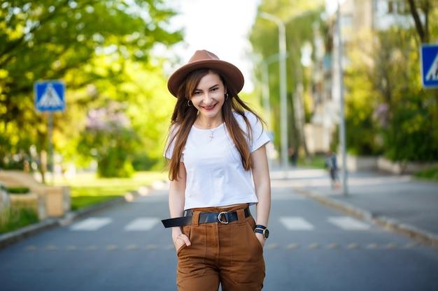 Een mooi meisje met een bruine hoed en een wit t-shirt loopt op een warme zonnige dag op de weg. mooie jonge vrouw in een hoed met een glimlach op haar gezicht