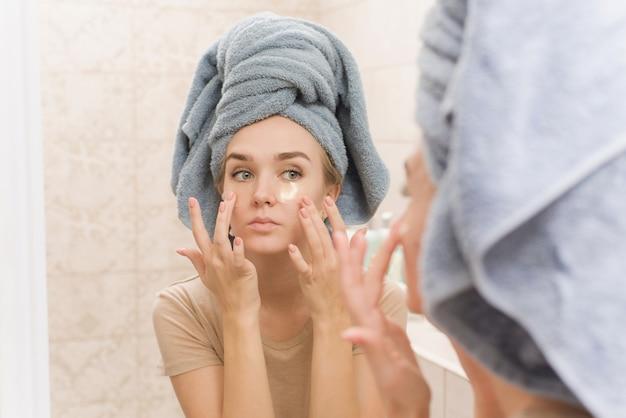 Een mooi meisje met een handdoek op haar hoofd plakt hydrogelpleisters onder haar ogen op haar gezicht.