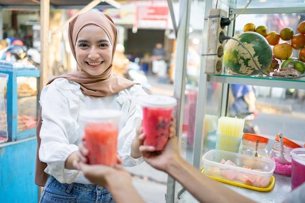 Een mooi meisje met een hoofddoek glimlacht naar de camera terwijl ze twee kopjes fruitijs pakt