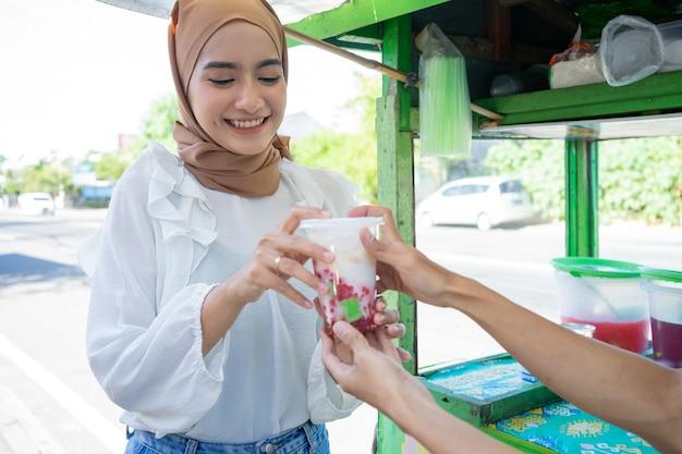 Een mooi meisje met een hoofddoek koopt es campur in een plastic zak