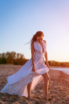Een mooi meisje met een kaukasisch uiterlijk staat alleen in een lange witte jurk aan de kust in de w...
