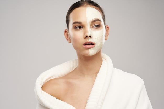Een mooi meisje met een masker tegen zwarte stippen op haar gezicht