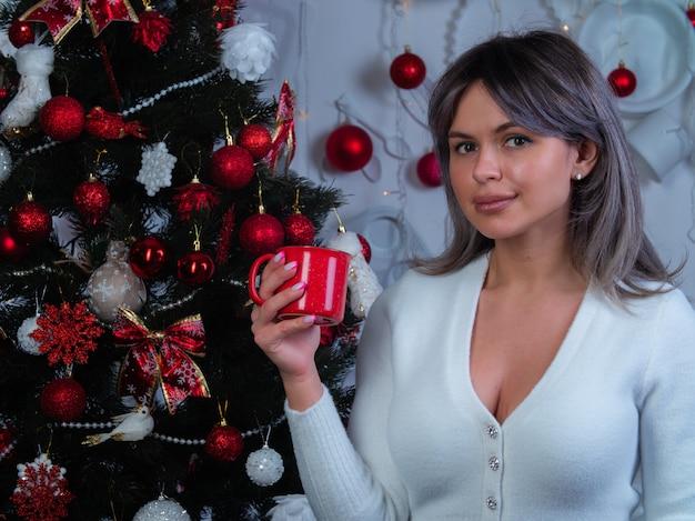 Een mooi meisje met een rode mok in haar handen ontmoet het nieuwe jaar en kerstmis bij de kerstboom