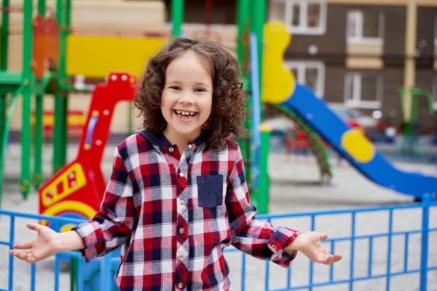 Een mooi meisje met krullend haar in een geruit overhemd op de speelplaats lacht en steekt haar handen naar de zijkanten