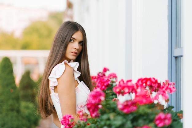 Een mooi meisje met lang blond steil haar staat in de buurt van de roze heldere bloemen