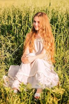 Een mooi meisje met lang haar en in een witte jurk zit in groene tarwe in een veld