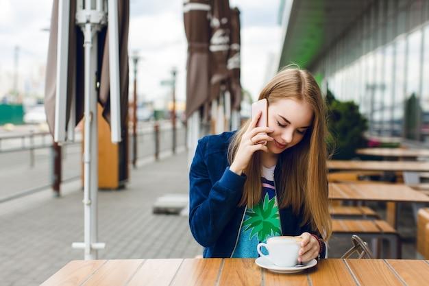 Een mooi meisje met lang haar zit aan de tafel op het terras. ze praat aan de telefoon en houdt een kopje koffie vast.