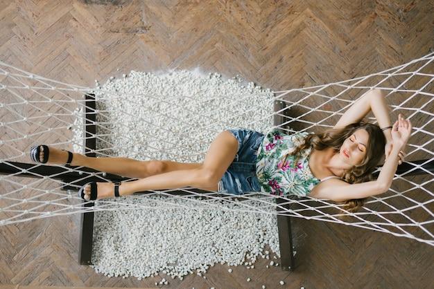 Een mooi meisje met lange slanke benen ligt in een hangmat en rust, slaapt en ontspant in denimgordijnen en een top