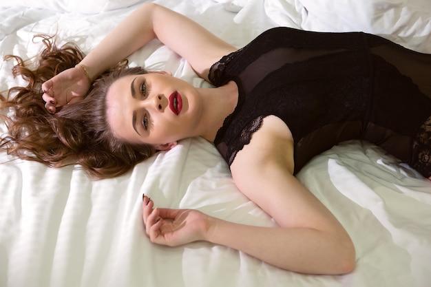 Een mooi meisje met prachtig donker haar ligt op een rechtgetrokken bed in sexy ondergoed