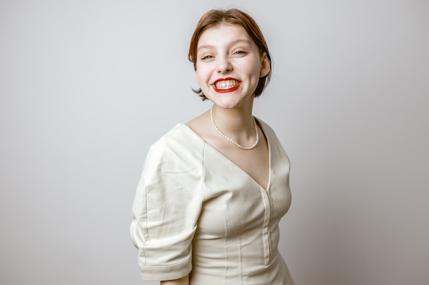 Een mooi meisje met rode lippen lacht met witte tanden