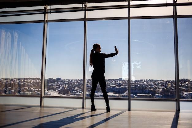 Een mooi meisje neemt een selfie op haar telefoon tegen de achtergrond van panoramische ramen in een wolkenkrabber. selectieve focus