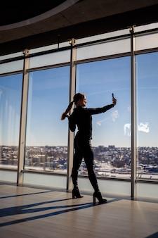 Een mooi meisje neemt een selfie op haar telefoon tegen de achtergrond van panoramische ramen in een wolkenkrabber