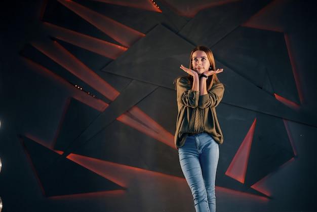 Een mooi meisje poseert de fotograaf op de achtergrond van een zwarte muur en een rode achtergrondverlichting.