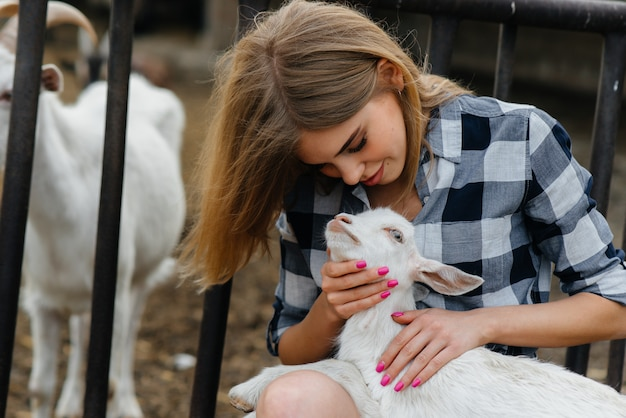 Een mooi meisje poseert op een boerderij met geiten en andere dieren. landbouw, veeteelt.