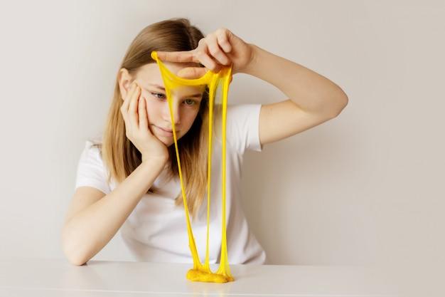 Een mooi meisje speelt een zelfgemaakt speeltje genaamd slijm