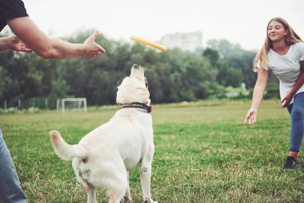 Een mooi meisje speelt met haar geliefde hond in het park.