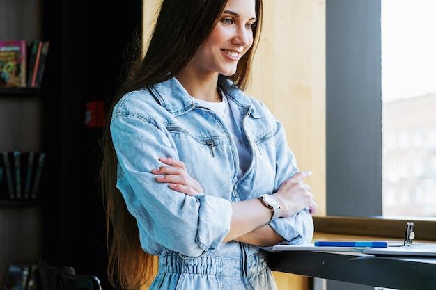 Een mooi meisje staat in een pose bij het raam voor de computer met haar armen gekruist op haar borst.