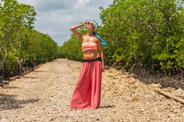 Een mooi meisje staat op de onverharde weg tussen de mangroven op een heldere zonnige dag op het eiland zanzibar, tanzania, afrika