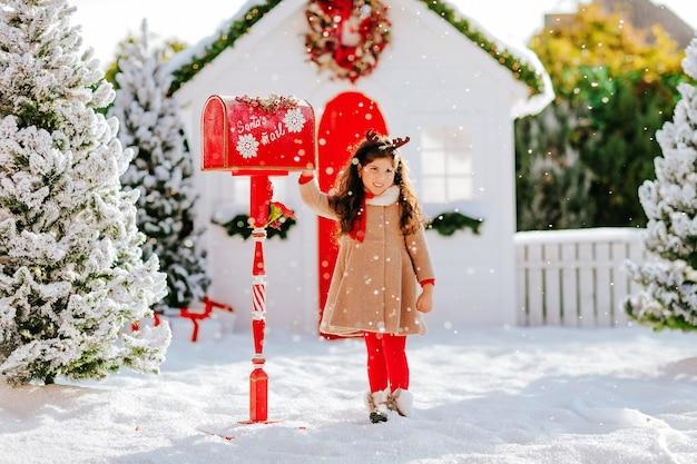 Een mooi meisje stuurt een brief naar de kerstman in een rode brievenbus