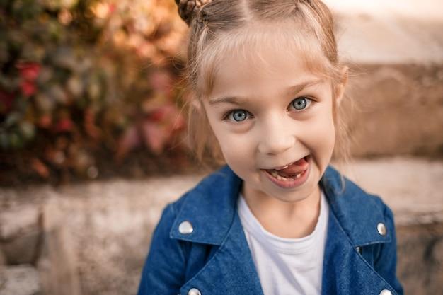 Een mooi meisje van een jaar of zeven in een spijkerjasje kijkt naar de camera en trekt gezichten