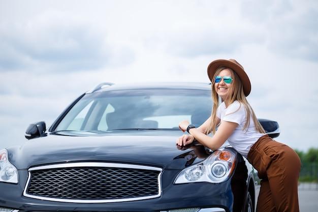 Een mooi meisje van europees uiterlijk met een bril en een bruine hoed staat in de buurt van een zwarte auto. fotoshoot bij de auto.